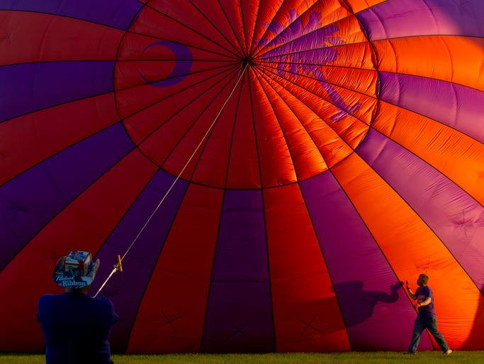 Mark Powers, left, steadies the Palmetto Paws balloon while Jeff Simmons checks its inflation during the 3rd annual Balloons Over Paradise Festival at Seminole Casino in Immokalee. The event also included balloon rides, arts and crafts vendors, a car show, a polo demonstration, anda concert. The event continues on Sunday starting at 6 a.m.