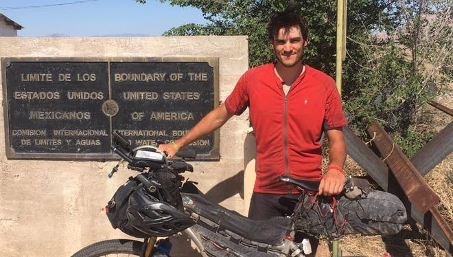 Peter Kraft Jr. poses at the U.S-Mexico border in New Mexico after finishing the Tour Divide.