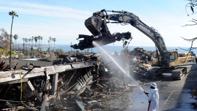 Crews work to clear debris from a Ventura apartment complex burned in the Thomas Fire.