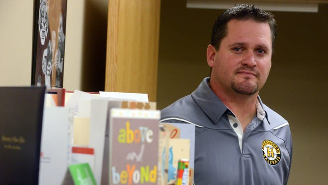 Harrisburg high school assistant principal, Ryan Rollinger, stands with some of the cards he has received thanking him for his role in stopping Mason Buhl after the shooting at the school last in 2015.