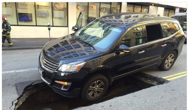 A photograph published on Twitter shows an SUV balanced over a sinkhole.