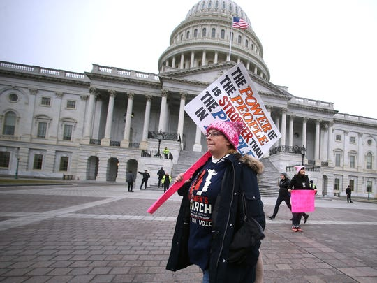 Kathy Adam of Green Brook walks past the U.S. Capital on her way to march in Washington, D.C.joining tens of thousands in the Women's March on Washington, held the day after Donald Trump's inauguration. Organizers of the march say they want to greet Trump's presidency by making a statement that women's rights are human rights.