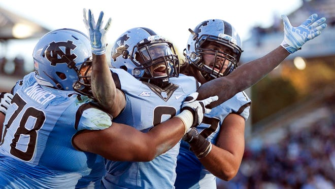 North Carolina's T.J. Logan, center, celebrates the game-winning touchdown after a one-yard run with teammates Landon Turner (78) and John Ferranto  against Pittsburgh on Nov. 15, 2014. The Tar Heels will face Rugters in the inaugural Quick Lane Bowl in Detroit on Dec. 26.