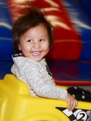 Azalea Myerson, 2, zips by in a race car at Farmington Play Day on Tuesday  at 1601 North Dustin Ave., Suite F.