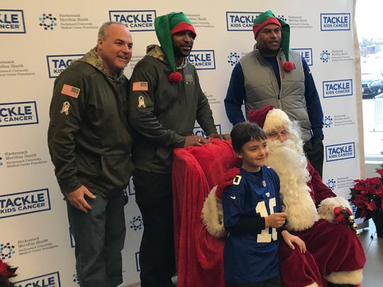 Stephen Bellairs and his son Sean with Giants David Tyree and Antonio Pierce and Santa