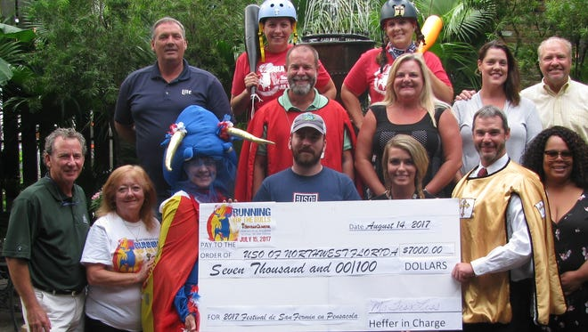 The USO of Northwest Florida receives a $7,000 check from the annual Running of the Bulls.