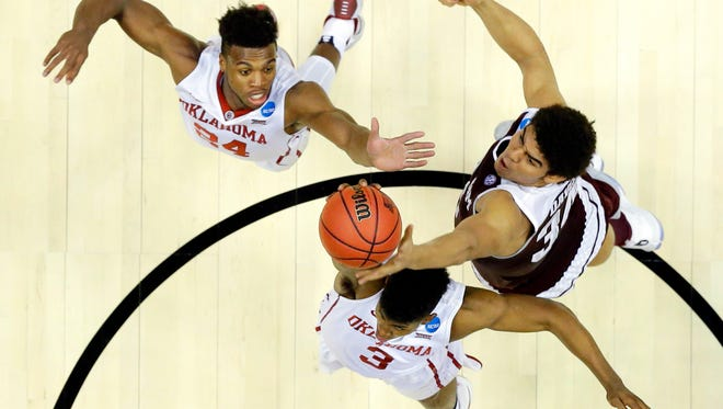 Texas A&M center Tyler Davis, right, pulls a rebound away from Oklahoma guard Christian James, bottom, and Buddy Hield during the first half of an NCAA college basketball game in the regional semifinals of the NCAA Tournament, Thursday, March 24, 2016, in Anaheim, Calif. (AP Photo/Gregory Bull)