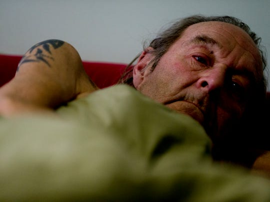 David Duvall lies in bed at his home in rural Cocke County, Tennessee, on Wednesday, Dec. 6, 2017. He was diagnosed last year with cancer; he's since had a lung removed and undergone chemotherapy but is now on hospice care.