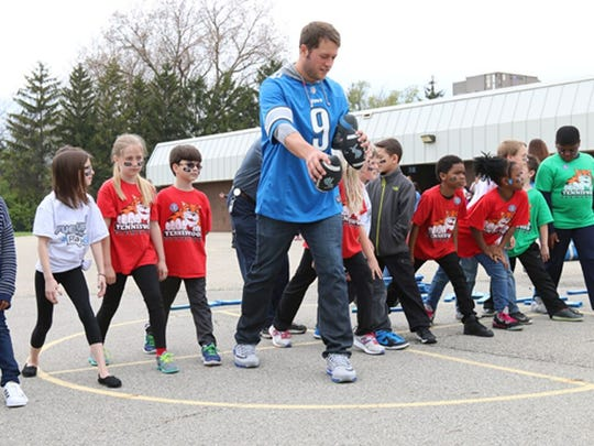 Lions quarterback Matthew Stafford plays with students