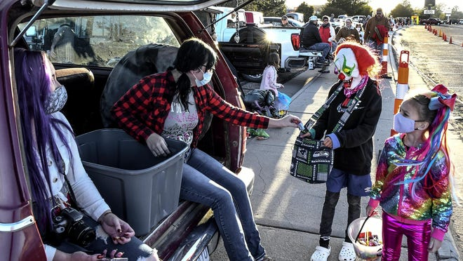 Anne Aeschliman, left, and Jayden Patterson hand out candy to children lined along the sidewalk Saturday at the Clarion inn parking lot during the Kansas Kruisers car club's annual Trunk and Treat event.