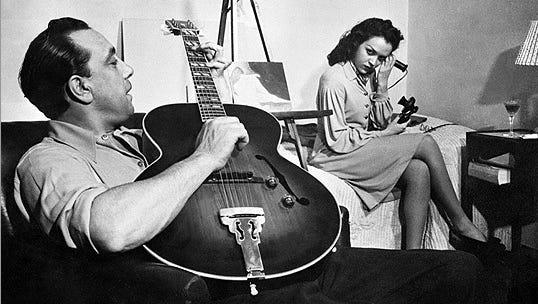 Django Reinhardt plays guitar in a Paris hotel room in 1945.