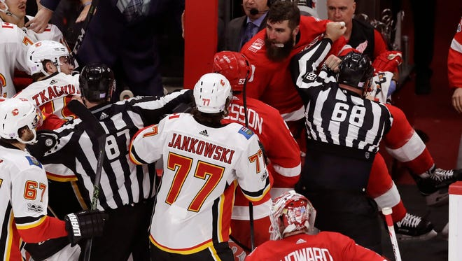Linesman Scott Driscoll (68) keeps Red Wings right wing Luke Witkowski (28) away from the Flames' in the third period Wednesday.