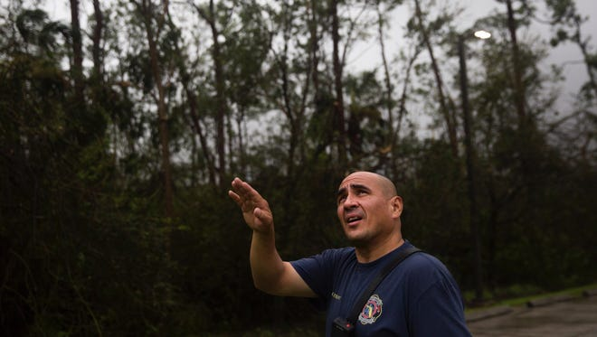 Lieutenant Manny Arroyo points up to the tree line as he ventures out in the eye of Hurricane Irma at the Greater Naples Fire Rescue Station 72 on Sunday, September 10, 2017.  Arroyo wanted to check for the family of deer that lives behind the station.