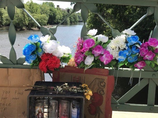 Flowers lay along Straight Street after a woman jumped off the bridge June 3.