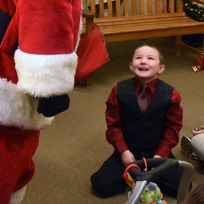 Gabrielle Lowery, 5, stares up at Santa Claus with