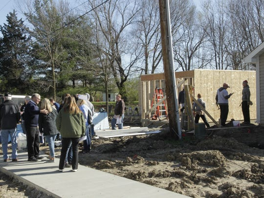 """A crowd gathers outside the Habitat for Humanity of Lafayette """"One More"""" build on Powder House Lane on April 8, 2017, in Lafayette."""