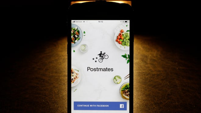 This Tuesday, Feb. 20, 2018, photo shows the Postmates app on an iPhone in Chicago. More fast-food companies have been offering delivery by teaming up with food ordering apps.