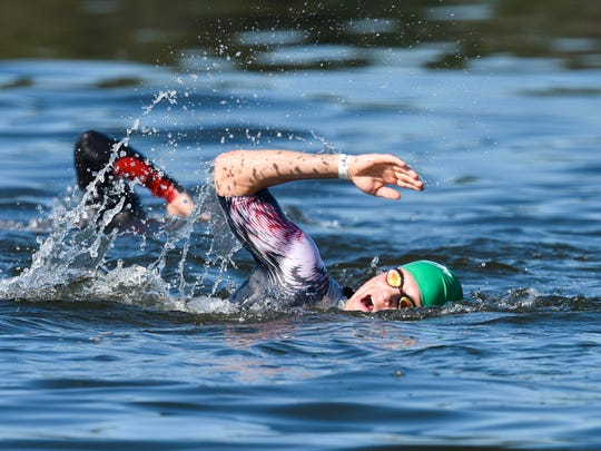 An athlete takes a breath swimming across Warner Lake during the first event of the Graniteman Triathlon in 2017 in Clearwater.