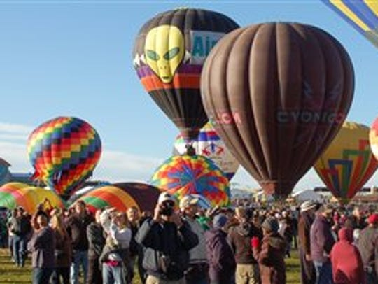 In this Oct. 8, 2011 file photo, spectators take photos of the hot air balloons at the Albuquerque International Balloon Fiesta before take off.