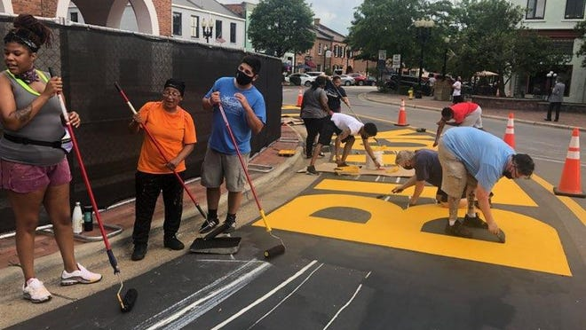Volunteers help clean and repaint murals that say, Black Lives Do Matter and End Racism Now, at the historic Market House in downtown Fayetteville after they were vandalized with white paint in July.