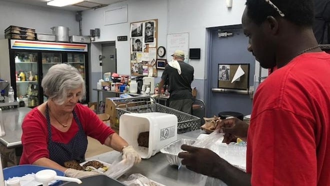 Volunteer Libby Westerbeke hands a plate of food to Herson Sterling at The Soup Kitchen west of Boynton Beach before a 2017 hurricane.