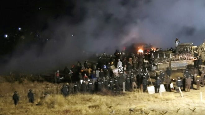 FILE - In this Nov. 20, 2016 file photo, provided by Morton County Sheriff's Department, law enforcement and protesters clash near the site of the Dakota Access pipeline on Sunday, Nov. 20, 2016, in Cannon Ball, N.D. A federal judge on Monday, July 6, 2020 sided with the Standing Rock Sioux Tribe and ordered the Dakota Access pipeline to shut down until more environmental review is done.