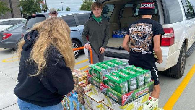 Volunteers with the Prosper Ladies Association stack donations of food on a cart. The supplies are used to feed local children participating in the organization's annual Summer Lunch Program.