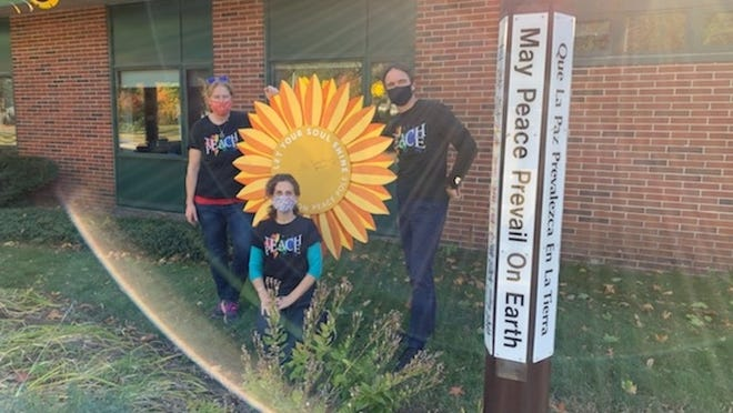 Jessica Wilke, music teacher; Kate Blehar, art; and Michael Walsh, physical education, at the giant sunflower next to the Houghton Elementary peace pole.