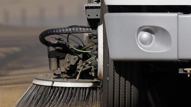 In this file photo, a sweeper truck clears a section of road.