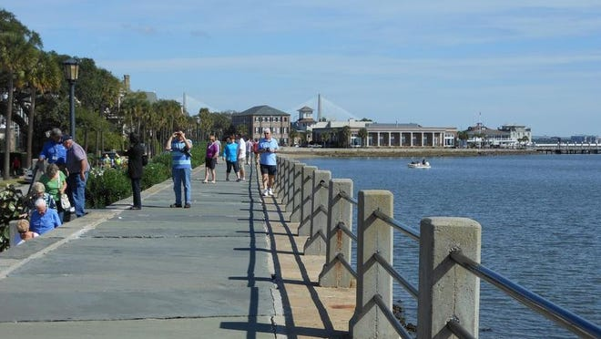Visitors stroll on the promenade along the Battery, which offers views of Charleston Harbor on one side and, on the other side, a line of stately antebellum homes in Charleston, S.C.