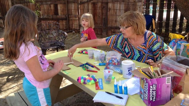 Rebecca Navarre helps granddaughter Claire Navarre, center, and Ella Beirne, both 6, with their art creations during the Agnes Pelton Society's Walking Tour of Historic Cathedral City Cove Homes and Artists in Cathedral City in 2014.