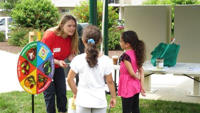 An intern at Cornell Cooperative Extension Dutchess County plays nutrition trivia with Beacon children at the Summer Meals Community event on July 10.