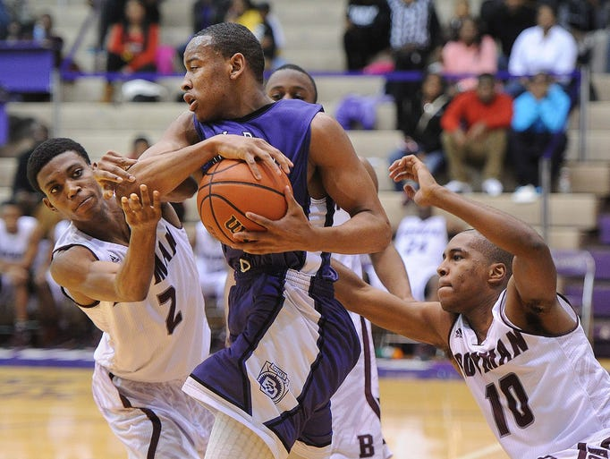 Stephon Matthews of BD is pressured by Bowman defenders Henry Taylor and DeShawn Franklin. Ben Davis defeated Bowman Academy 81-71 at Ben Davis Friday January 3, 2014.