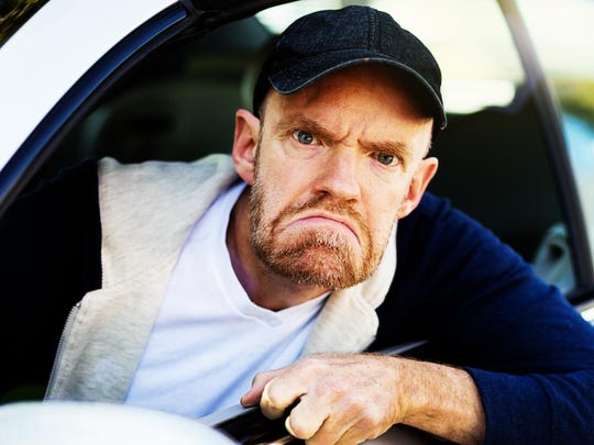 Angry male driver looks through car window, grimacing, fist clenched