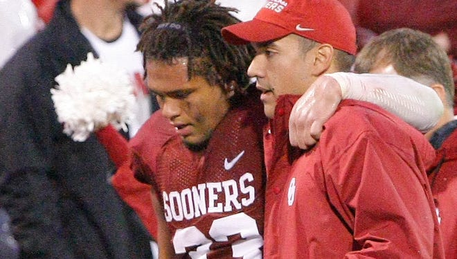 Oklahoma fullback Trey Millard is helped off the field Saturday after suffering a season-ending knee injury covering a fourth-quarter kickoff against Texas Tech.