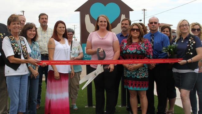 Surrounded by community officials and leaders Kid's Inc. Executive Director Melanie Gilmore prepares to officially cut the ribbon on the new Kid's Inc. Otero and Lincoln County Child Advocacy Center, 1108 Cuba Ave., Friday.