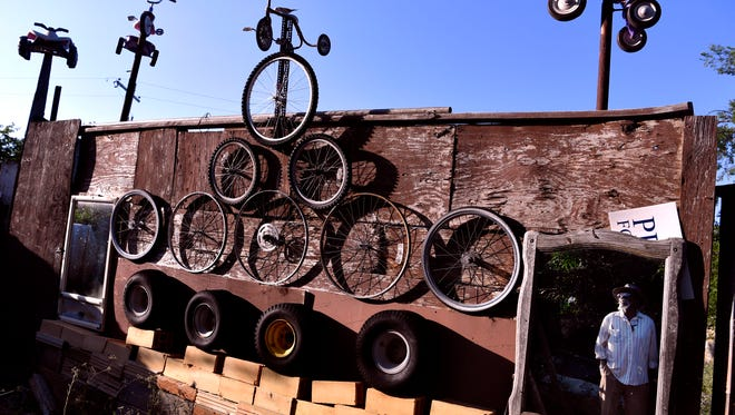 Ernest Johnson is framed in a mirror hanging amidst a display of wheels and tricycles at his Abilene home May 30. Johnson, 77, said creating art out of bits of junk is one of the things that keeps him going.