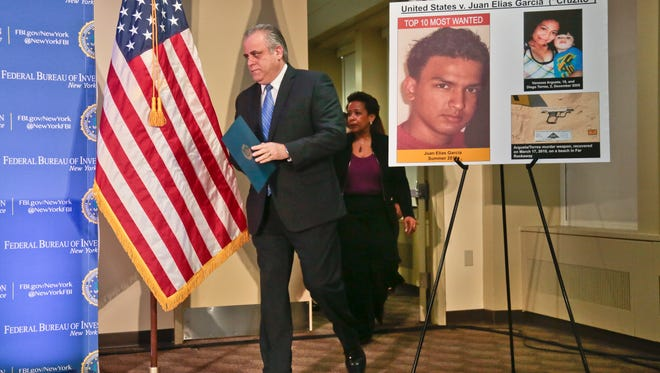 George Venizelos, left, the FBI assistant director of the New York field office, and Loretta Lynch, center, U.S. Attorney for the Eastern District of New York, walks past a display showing Juan Elias Garcia, left, and his alleged murder victims, Vanessa Argueta and her son Diego Torres, right, at a press conference, Wednesday March 26, 2014, in New York.
