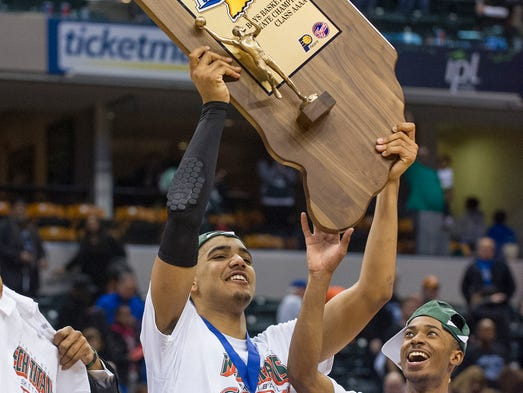 Arsenal Tech High School senior Trey Lyles holds up the team's State Championship trophy after winning the IHSAA Boys Basketball 4A State Finals at Bankers Life Fieldhouse, Saturday, March 29, 2014. Aresnal Tech defeated Lake Central 63-59.