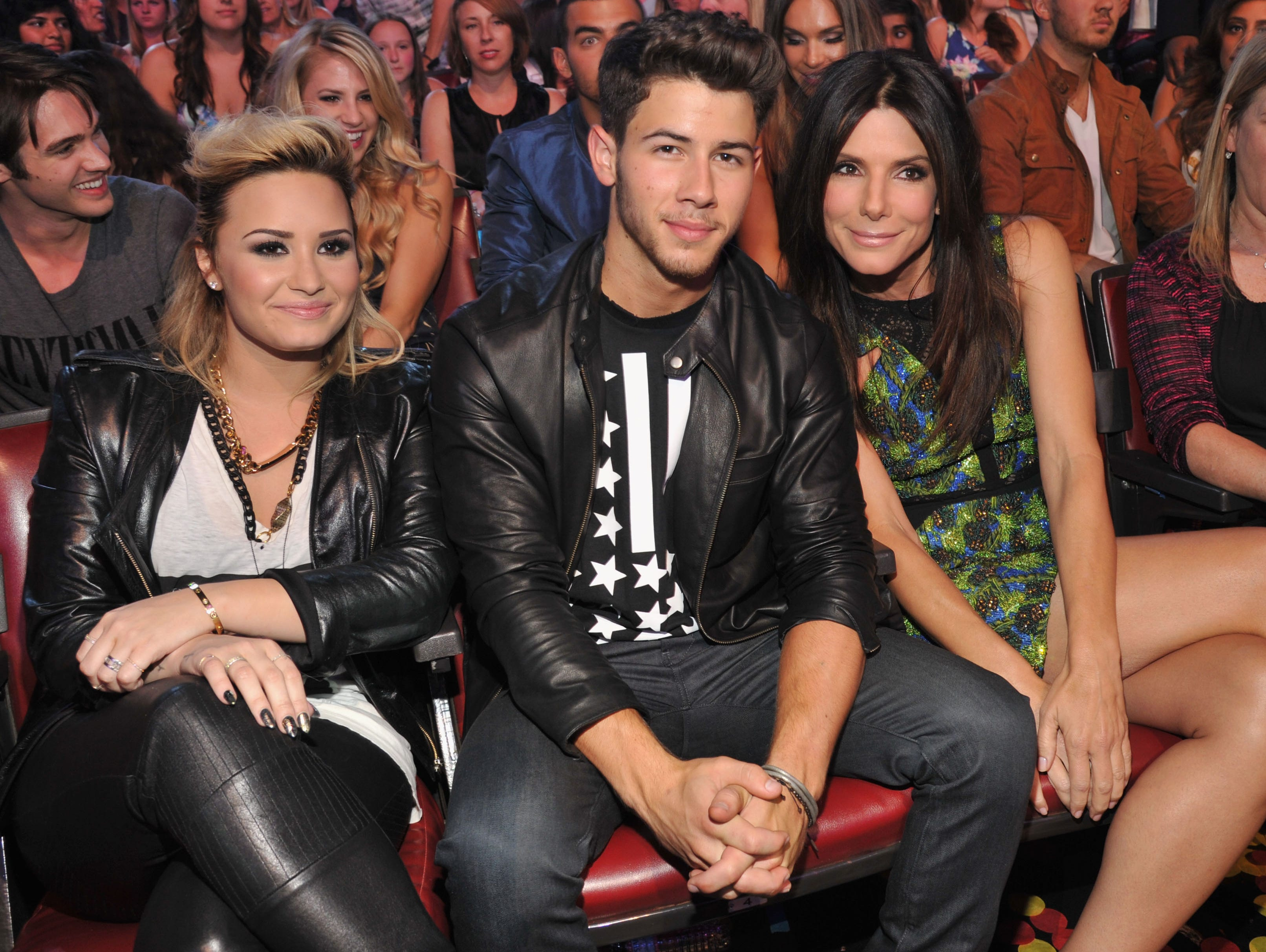 Musicians Demi Lovato, Nick Jonas, and actress Sandra Bullock  enjoy the show.