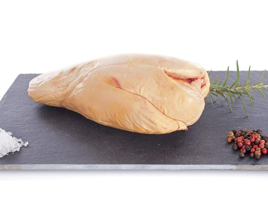 Close up of foie gras on grey tile cutting board