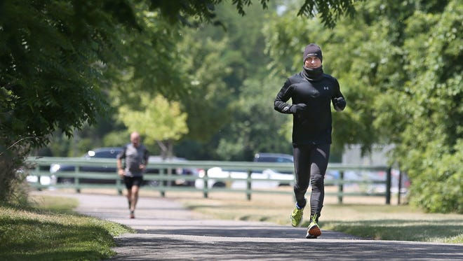 Brett Sobieraski, a sergeant with the Rochester Police Dept., heads out on a 8-mile training run from the  Monroe County Training Building Tuesday, July 12, 2016. Sobieraski, dressed in layers of warm winter running gear, is training for the 135-mile Badwater race through Death Valley next week.