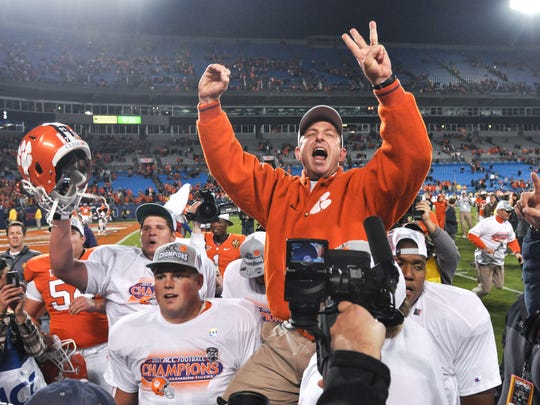 Clemson head coach Dabo Swinney holds up three fingers and a signals 0, as he is carried by Clemson offensive linemen Landon Walker, right, and others following a 38-10 win over Virginia Tech in the ACC Championship game at Bank of America Stadium in Charlotte, N.C. in December 2011.