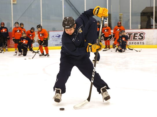 Coach Dillon Shaffer demonstrates a puck handling drill