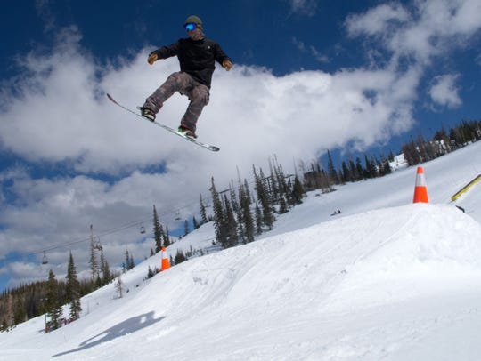 A snowboarder flies off of a jump in the terrain park