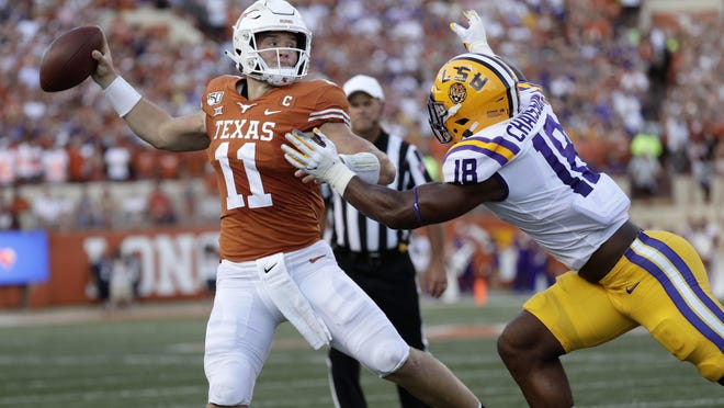 Texas quarterback Sam Ehlinger throws a pass as LSU linebacker K'Lavon Chaisson defends.