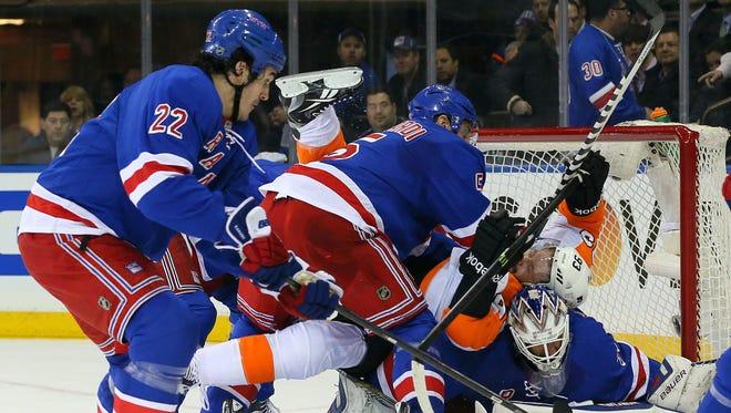 Rangers defenseman Dan Girardi, center, pushes Flyers forward Jakub Voracek onto goalie Henrik Lundqvist as forward Brian Boyle, left, looks on.