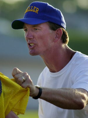 Moeller High School head football coach Bob Crable grabs one of his players by the jersey as he yells at him from the sideline during their scrimmage football game against Colerain High School Friday August 17, 2001.