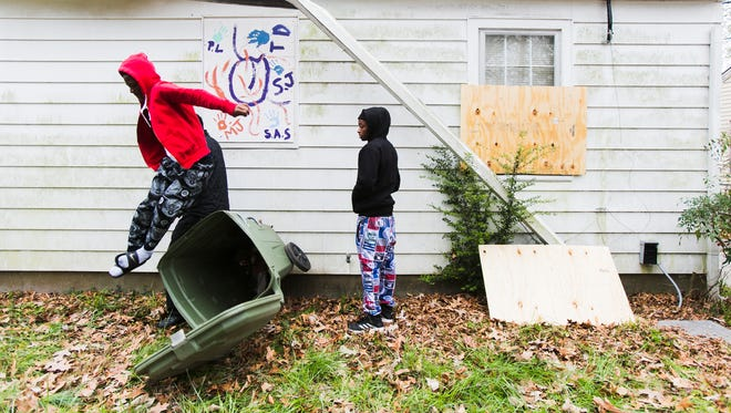 March 16, 2017 - Jaivan Hopson (right), 18, a graduate from Calvine High School in Sacramento, CA, watches Terry Davis, 14, a Douglass High School freshman, as he jumps from a trash can while the young men board up a vacant house on Manhattan Ave. in the Douglass neighborhood on Thursday morning. About 60 students from Douglass and Kingsbury high schools, along with volunteers from other youth groups spent most of their Spring Break fighting blight in North Memphis.