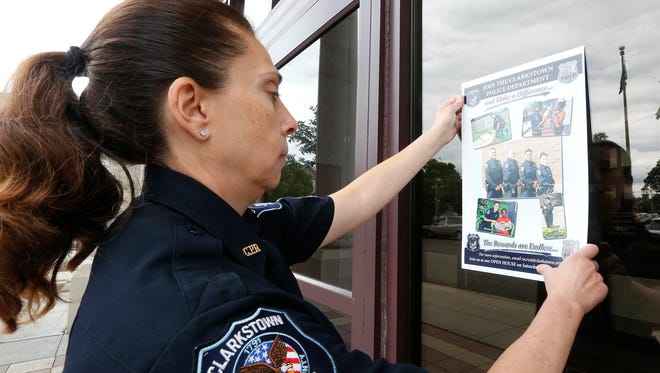 Clarkstown Police Sergeant Jo Anne Fratianni places a recruiting poster on the window at Clarkstown Police Headquarters on Tuesday, August 02, 2016.